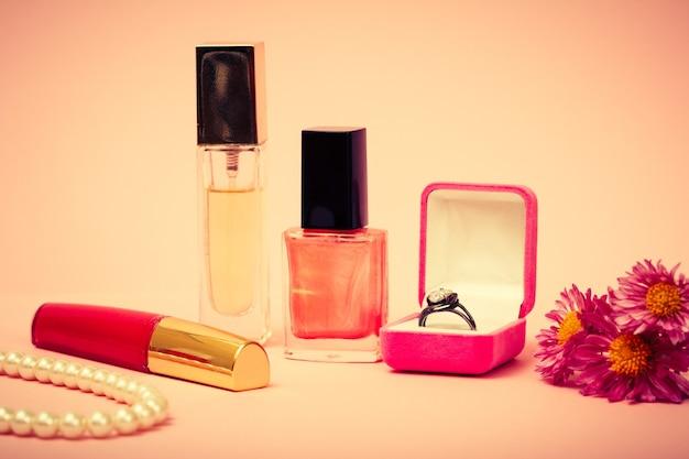 Ring in einer box, nagellack, parfüm, lippenstift, perlen und blumen auf rosa hintergrund. damenschmuck, kosmetik und accessoires. farbe getönt.