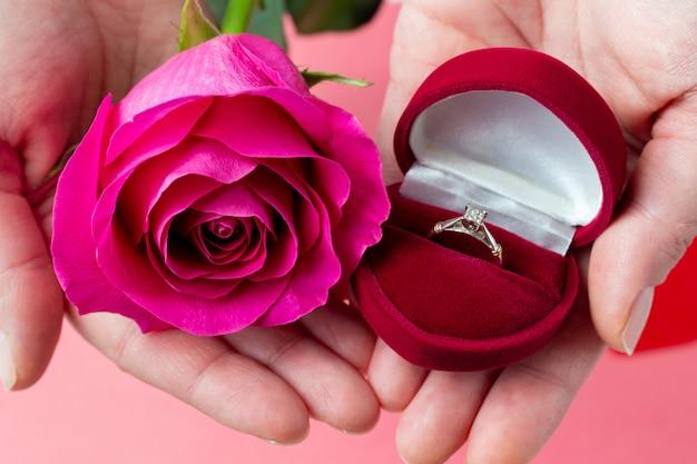 Ring in herzförmiger schachtel und blume in händen. valentinstag geschenk