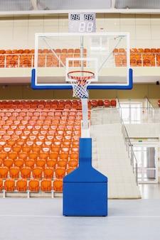 Ring und schild zum basketballspielen. orange stühle stehen in einer reihe in einem überdachten stadion. tribüne für fans