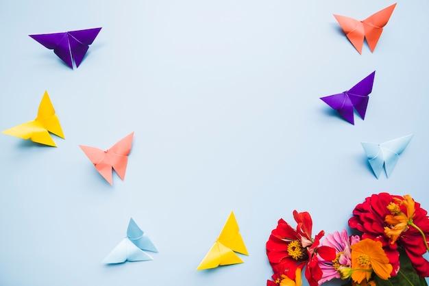 Ringelblumenblumen und origamipapierschmetterlinge auf blauem hintergrund