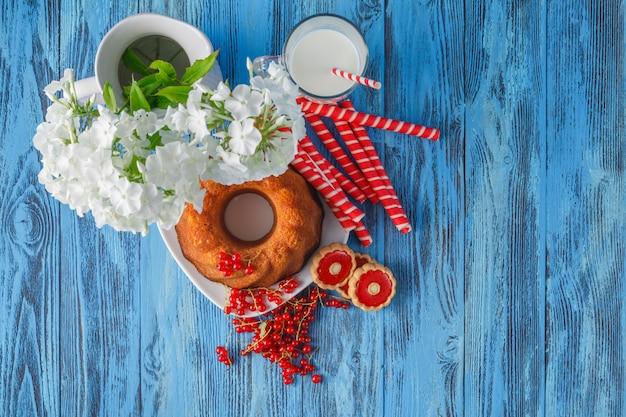 Ringkuchen mit rosinen, beeren, becher auf holztisch
