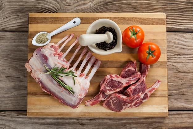 Rippenständer, rippenkoteletts und zutaten auf holzbrett