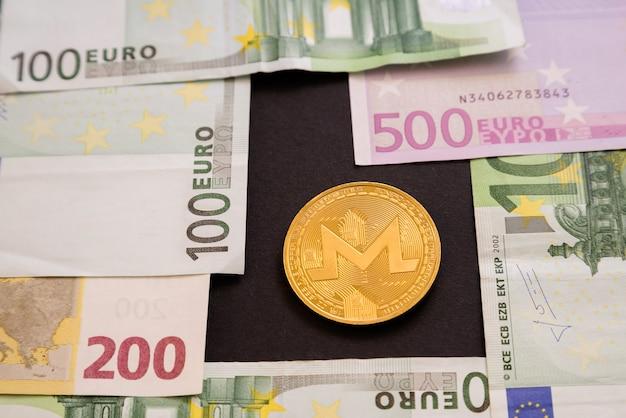 Ripple-münze neben euro-banknoten auf schwarzer oberfläche.