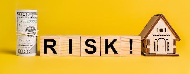 Risiko mit hausminiaturmodell und geld auf gelbem grund. das konzept von geschäft, finanzen, kredit, steuern, immobilien, haus, wohnen