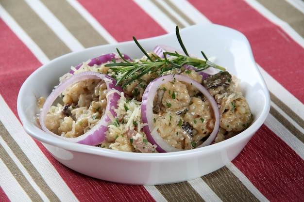 Risoto milanese mit aromatischem safranreis, kirschtomate, pilzen und gewürfeltem gemüse für ein köstliches herzhaftes italienisches gericht, nahaufnahme.