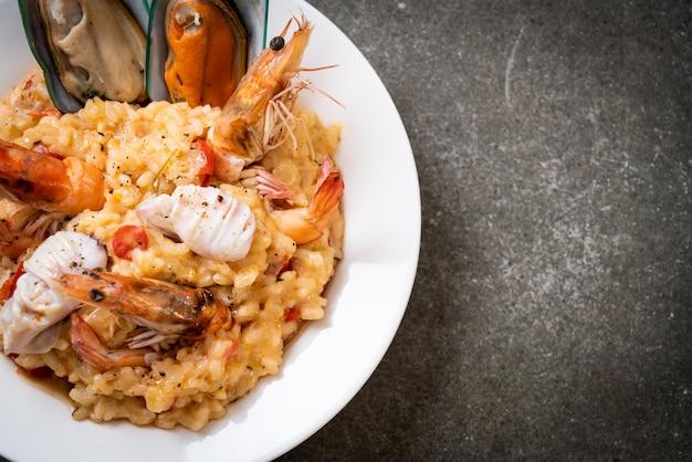 Risotto mit meeresfrüchten (garnelen, muscheln, kraken, muscheln) und tomaten