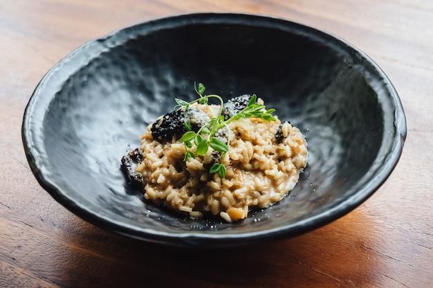 Risotto mit pilz, frischem kraut und parmesankäseparmesankäse im schwarzblech auf holztisch.