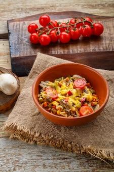 Risotto mit pilzen in einem teller auf einem hölzernen hintergrund auf einer leinenserviette neben tomaten auf einem brett.
