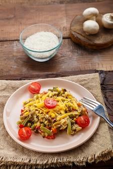 Risotto mit pilzen in einem teller auf holzuntergrund auf einer leinenserviette und einer gabel und zutaten.