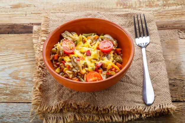 Risotto mit pilzen in einer tonplatte auf einem hölzernen hintergrund auf einer leinenserviette neben einer gabel.