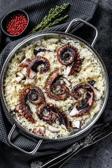 Risotto mit tintenfischtentakeln in einer pfanne.