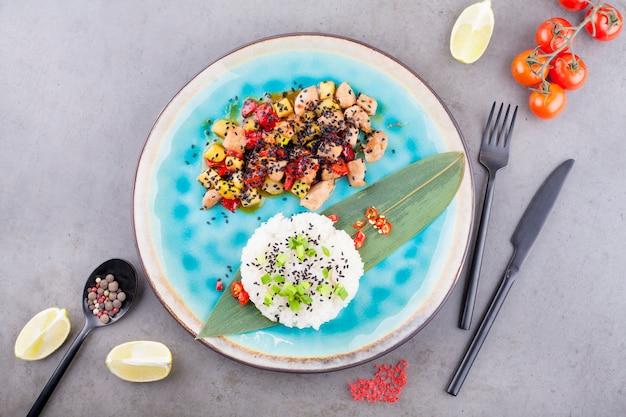 Risotto, reis, serviert auf einem palmblatt neben einer füllung aus gemüse und fleisch, auf grauem hintergrund, neben limettenscheiben und kirschtomaten. das konzept der rezepte oder menüs