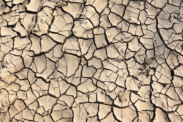 Rissiger boden für hintergrund- und texturmaterial, trockenes wasserloses gebiet, klimawandelkonzept