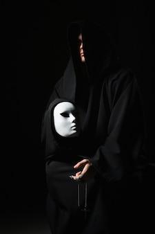 Ritus des umgangs mit dem teufel. sünder in schwarzer kleidung und dämon im ärmel. vom teufel besessener mensch. der böse zauberer spricht mit der maske. schizo spricht zu sich. verfluchter attentäter in einem dunklen raum. bösartiger magier.