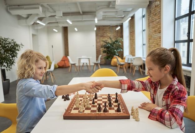 Rivalität zwei kleine kinder jungen und mädchen händeschütteln nach dem spiel beim brettspiel sitzen
