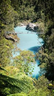 River gorge mit türkisfarbenem wasser und drehbrücke, die darüber führt hokitika gorge new zealand Premium Fotos