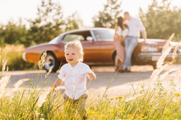 Riviera im retro-stil. einzigartiges auto bei sonnenuntergang. die eltern stehen in der nähe des autos und küssen sich im hintergrund. der sohn spielt und rennt vor ihnen weg.