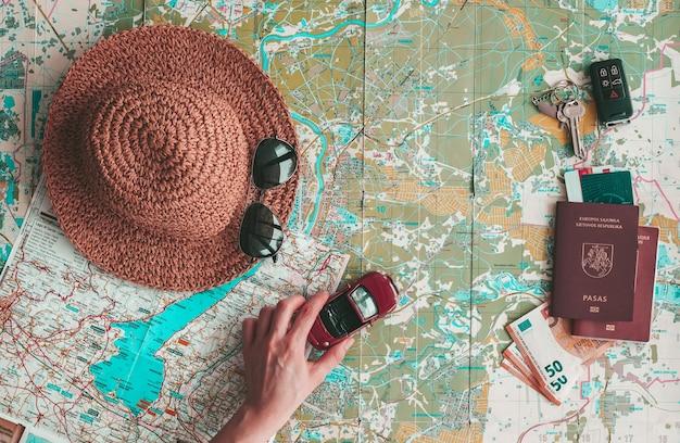 Road trip konzept flach lag. hand, die ein spielzeugauto auf kartenerkundung hält. hut, sonnenbrille, reisepass, geld und schlüssel auf der straßenkarte. urlaub planen.