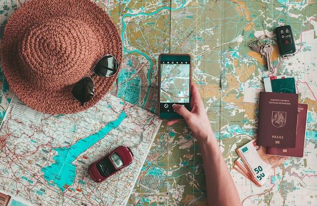 Road trip konzept flach lag. hand, die ein telefon auf der kartenerkundung hält. hut, sonnenbrille, spielzeugauto, reisepass, geld und schlüssel auf der straßenkarte. urlaub planen.