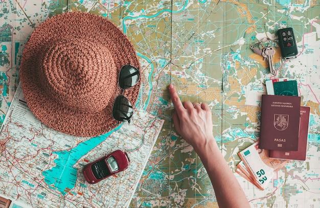 Road trip konzept flach lag. hand zeigt auf einen ort auf der karte. hut, sonnenbrille, spielzeugauto, reisepass, geld und schlüssel auf der straßenkarte. urlaub planen.
