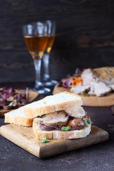 Roastbeefsandwich mit gemüse, meister und kräutern auf hölzernem schneidebrett, rustikale art.