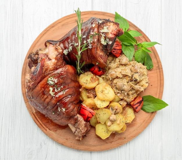 Roaster pork knuckle mit wirsing und ofenkartoffeln