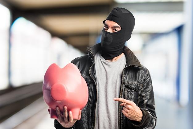 Robber hält ein sparschwein