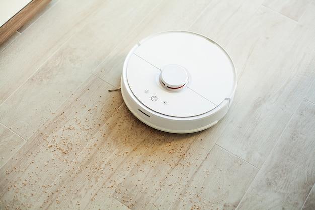 Roboter-staubsauger führt zu einer bestimmten zeit eine automatische reinigung der wohnung durch. intelligentes zuhause.