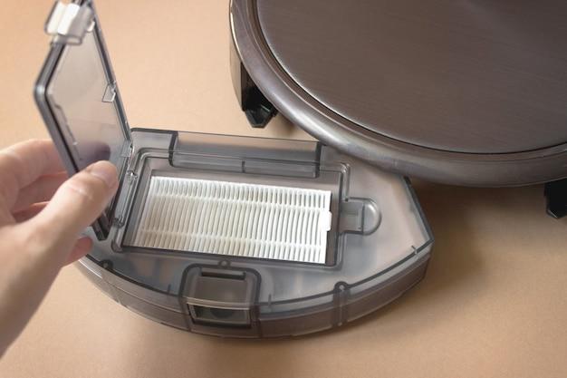 Roboter-staubsauger hautnah. frau reinigt automatischen roboterstaubsauger des mülleimers.