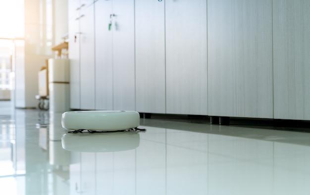 Roboter-staubsauger-reinigungsboden im büro. weißer roboterstaubsauger für das smart home konzept. reinigungsroboter zum reinigen des bodens. kabelloses gerät. intelligente reinigungstechnologie. haushaltsgerät.