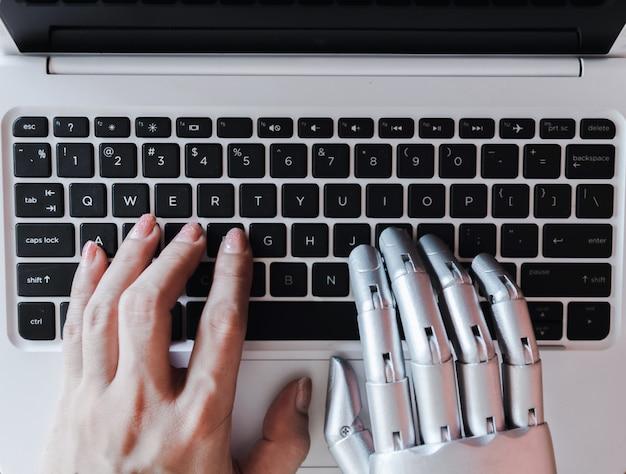 Roboterhände und -finger zeigen auf laptopknopf-berater chatbot roboterkonzept der künstlichen intelligenz