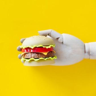 Roboterhand, die einen hamburger durchbohrt