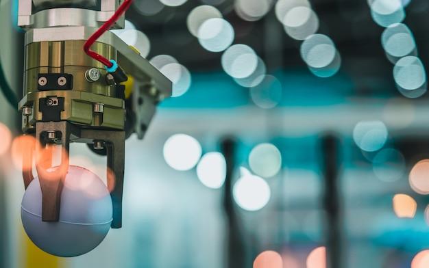 Roboterhandmaschine, die weißen ball auf bokeh hintergrund in der fabrik aufhebt