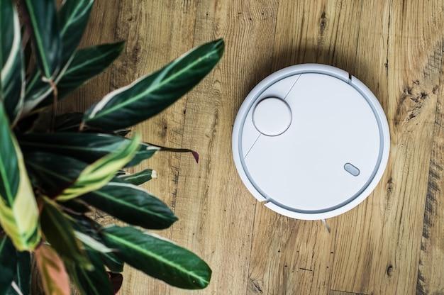 Roboterstaubsauger auf bretterboden. der blick von oben. smart-home-konzept. automatische reinigung