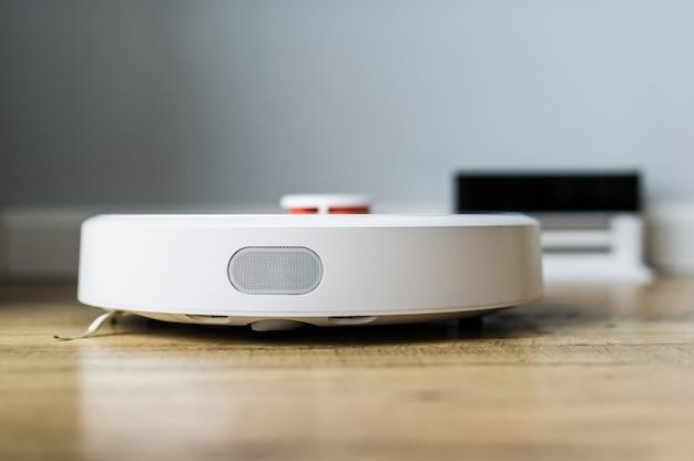 Roboterstaubsauger auf bretterboden. seitenansicht. smart-home-konzept. automatische reinigung
