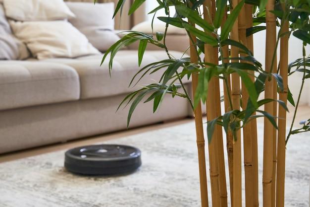 Roboterstaubsauger auf dem boden im gemütlichen modernen wohnzimmer