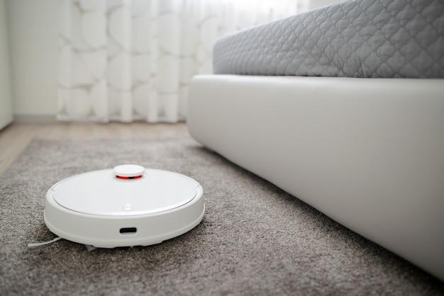 Roboterstaubsauger, der den raum reinigt. roboterstaubsauger arbeiten auf teppich. intelligente reinigungstechnologie.