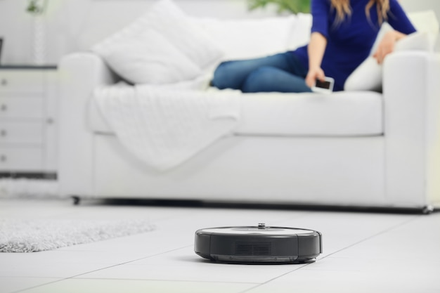 Roboterstaubsauger, der den raum säubert, während sich die frau auf dem sofa ausruht