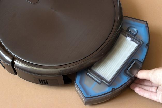 Roboterstaubsauger ersetzt einen behälter. roboterstaubsauger auf braunem hintergrund. nahaufnahme.