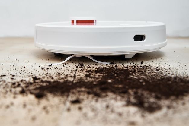 Roboterstaubsauger reinigt schmutz auf dem boden.