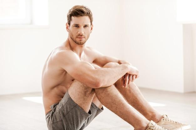 Robust und gutaussehend. hübscher junger mann ohne hemd in shorts, der auf dem boden sitzt