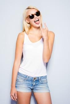 Rock and roll-königin. schöne junge blonde haarfrauen, die ein gesicht machen und gestikulieren, während sie vor grauem hintergrund stehen