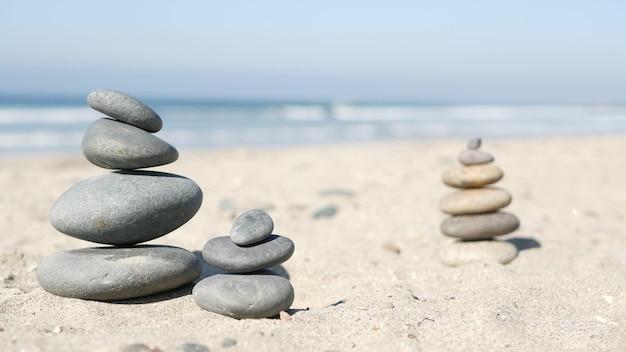 Rock balancieren am ozeanstrand, steine stapeln sich durch meerwasserwellen. pyramide von kieselsteinen am sandigen ufer. stabiler haufen oder haufen im weichzeichner mit bokeh, nahaufnahme. zen-balance, minimalismus, harmonie und frieden