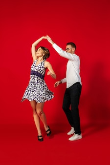 Rock 'n' roll. altmodische junge frau, die lokalisiert auf rotem studiohintergrund tanzt. junger stilvoller mann und frau.