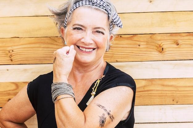 Rock und alternative fröhliche ältere kaukasische frau zeigen ihr tattoo auf dem arm lächelnd
