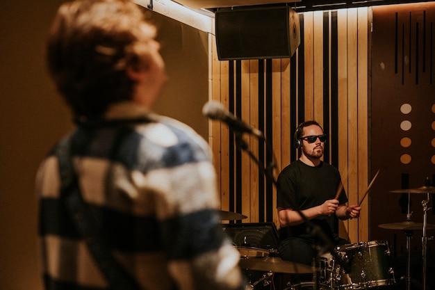 Rockband-schlagzeuger, der wiederholung im aufnahmestudio durchführt