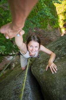 Rockclimber, der weiblichem bergsteiger hilft, spitze des berges zu erreichen