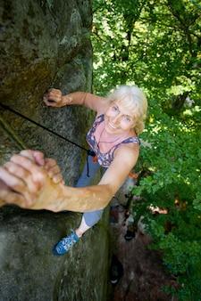 Rockclimber, der zum weiblichen bergsteiger hilft, spitze des berges zu erreichen