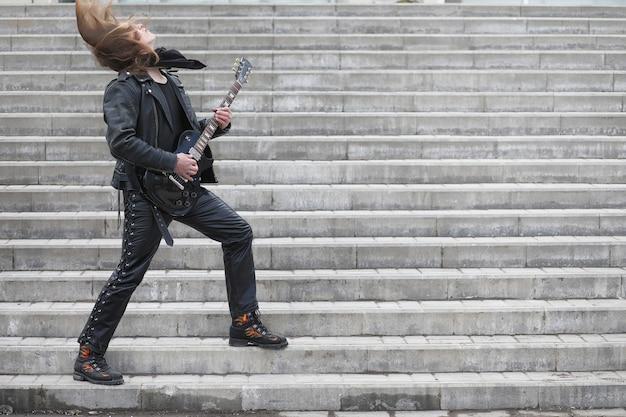 Rockgitarrist auf den stufen. ein musiker mit einer bassgitarre in einem lederanzug. metalist mit gitarre vor dem hintergrund des industrieschritts.