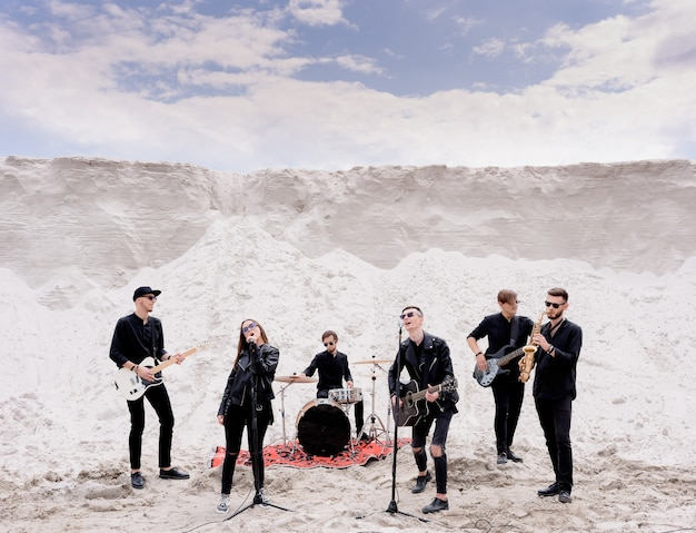 Rockmusikband, die ein konzert am strand aufführt
